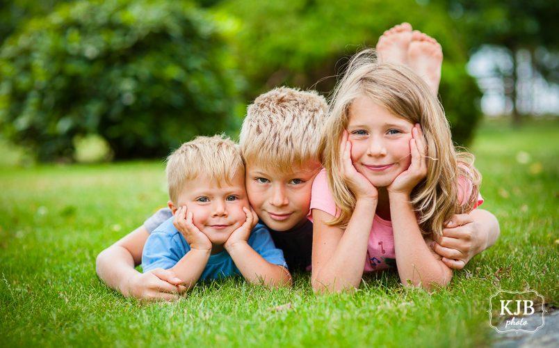Jarní focení dětí - tři děti leží na trávě